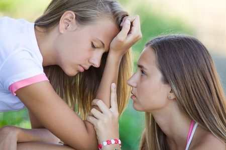 young girl comforting her friend in a depression Stock Photo