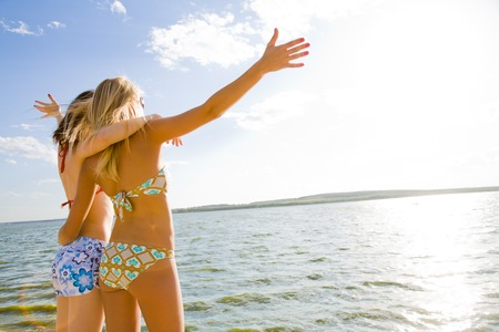 two beautiful young girlfriends opened her hands with delight at the blue sea and sky Stock Photo