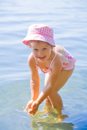shallow water: Happy little girl having fun, swimming  at shallow water