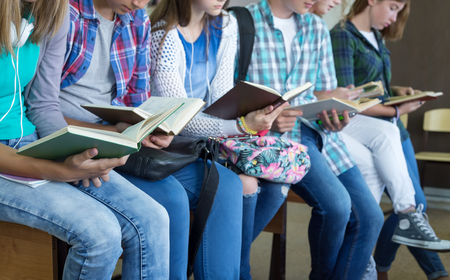 teens: Teenage students in library reading books Stock Photo