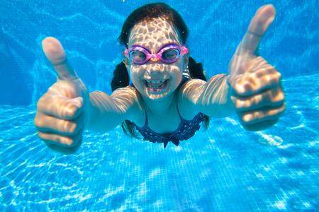 chicas sonriendo: niña se sumerge en el agua y muestra el gesto de OK Foto de archivo
