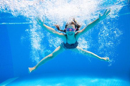 ni�os sanos: ni�a crea burbujas bajo el agua en la piscina