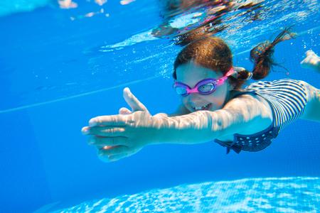 swim goggles: little girl deftly swim underwater in pool Stock Photo