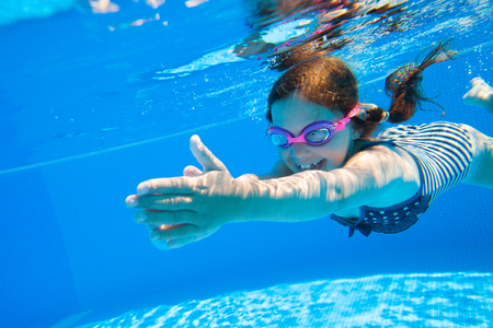 niños nadando: niña hábilmente nadar bajo el agua en la piscina