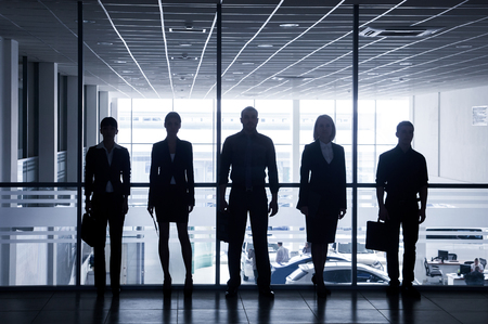 executive woman: silhouettes of business people rushing for the large windows in the background