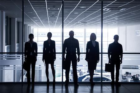 silueta hombre: siluetas de personas de negocios que corren por las grandes ventanas en el fondo