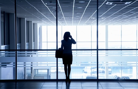 phone professional: Silhouette of a woman standing alone against the backdrop of large windows office