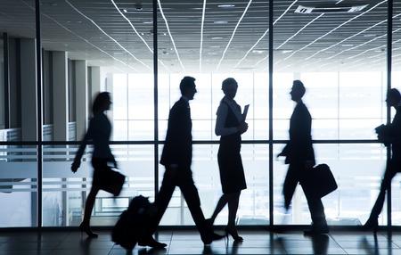 empleados trabajando: siluetas de personas de negocios que corren por las grandes ventanas en el fondo