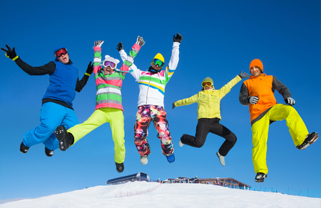 winter vacation: Five friends joyfully jump into the sky over snow drifts in the winter resort