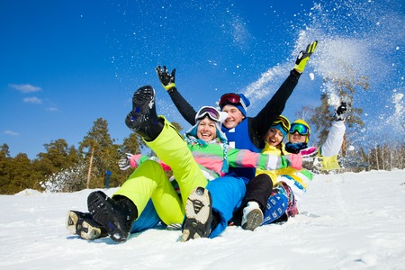 downhill: group of funny friends slide downhill together on mountain holiday Stock Photo