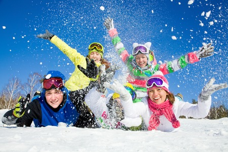 Group of teens playing on snow in ski resort Stockfoto