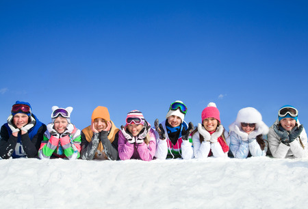 Group of teens lying on snow in ski resort Stock Photo - 52744119