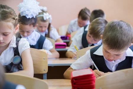 infancia: los escolares se sientan en sus escritorios en la escuela primaria Foto de archivo