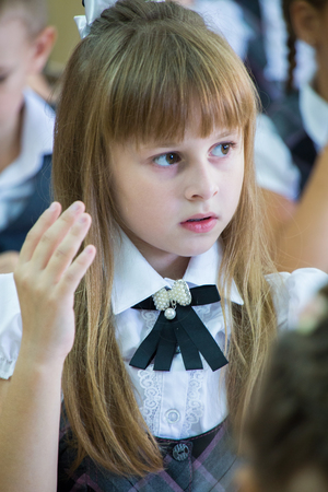 elementary age girl: schoolgirl sits at a school desk at a lesson at school Stock Photo