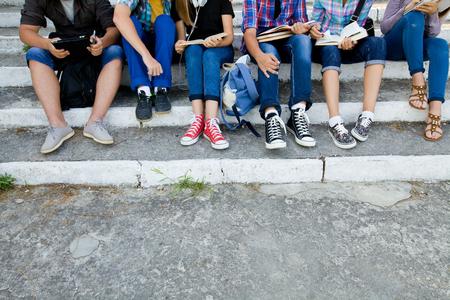 jovenes estudiantes: grupo de jóvenes estudiantes con libros y aparatos se sientan en los pasos en el parque. irreconocible