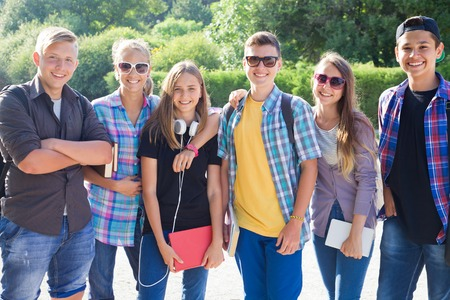 youth group: group of teenagers with textbooks and gadgets on background of green park Stock Photo