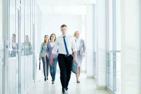 center city: businesspeople walking in the corridor of an business center, pronounced motion blur