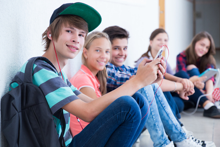 Grupa nastolatków siedzących na podłodze w korytarzu