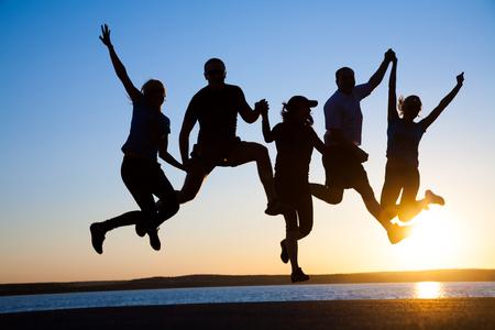 люди: Группа счастливых молодых людей прыгать на пляже на красивый летний закат