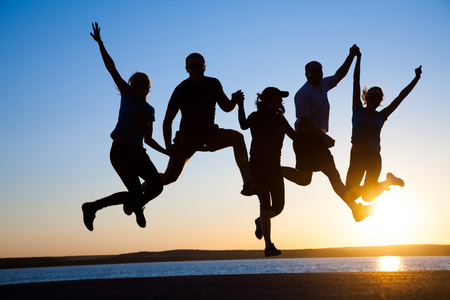 group of happy young people jumping at the beach on  beautiful summer sunset 스톡 콘텐츠
