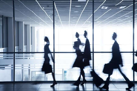silhouettes of business people rushing for the large windows in the background photo