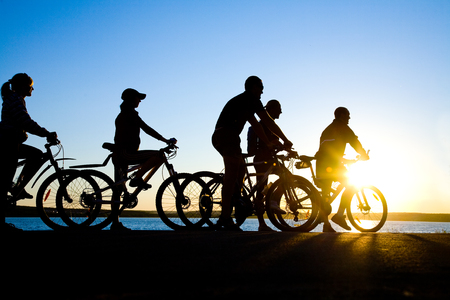Photo of sporty company friends on bicycles outdoors against sunset.