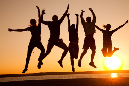 group of happy young people jumping at the beach on  beautiful summer sunset Stockfoto