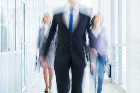 businesspeople walking in the corridor of an business center, pronounced motion blur photo