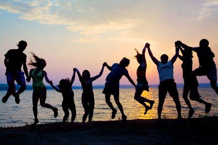 grote groep van gelukkige jonge mensen dansen op het strand op mooie zomerse zonsondergang