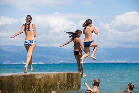 cliff jumping: group of young girls jumping from a pier into the sea. fun summer vacation