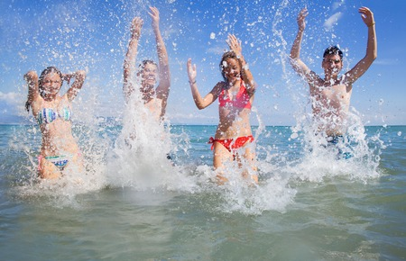 ragazze che ballano: giovani che ballano e che spruzzano in spiaggia sulla bella periodo estivo