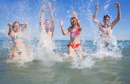 jovenes estudiantes: jóvenes bailando y rociado en la playa en tiempo de verano hermoso Foto de archivo