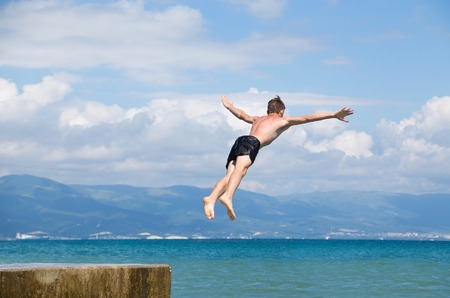 cliff jumping: Man jumping off cliff into the sea. Summer fun lifestyle. Stock Photo