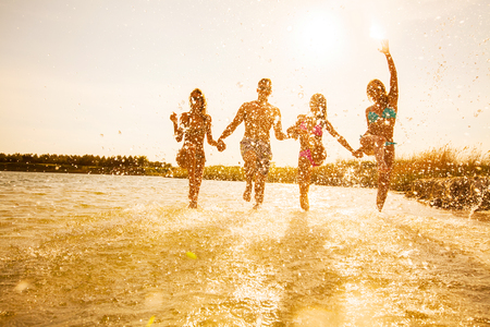 年轻人在美丽的夏日日落上在海滩上跳舞、喷水