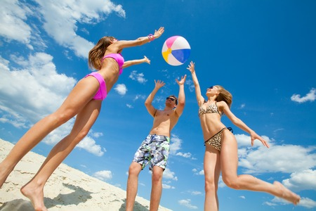 maillot de bain fille: Les jeunes gens amusants jouent à la balle sur la plage Banque d'images