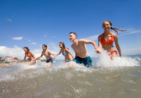water splashing: young people running and spraying at the beach on  beautiful summer time