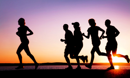 sun beach: group of young people runs at the beach on beautiful summer sunset Stock Photo