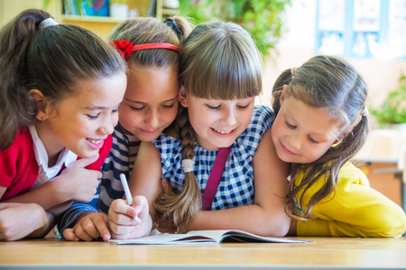 school notebook: girls from elementary school together decide to learn from notebook