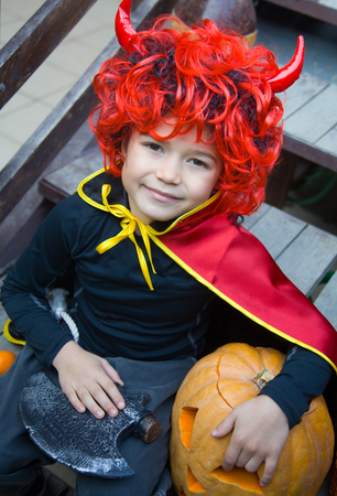 boy in a witch costume with halloween pumpkin on holiday