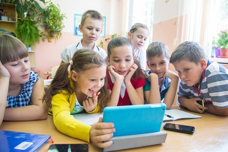 enrolled: Children of primary school are enrolled in the class of tablet Stock Photo