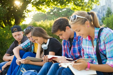 study group: group of young students with books and gadgets sit on the steps in the park