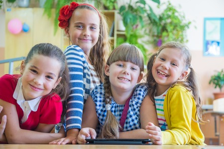 elementary age girl: girls  from elementary school together decide to learn from tablet Stock Photo