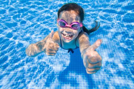 Cheerful little girl playing under  water in pool. Standard-Bild