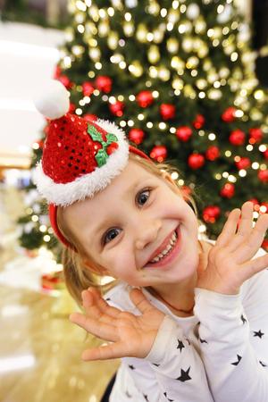 Portrait of little cute girl in Santa hat background christmas tree