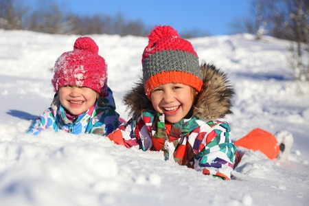 siblings: two little girls playing  on snow in winter time Stock Photo