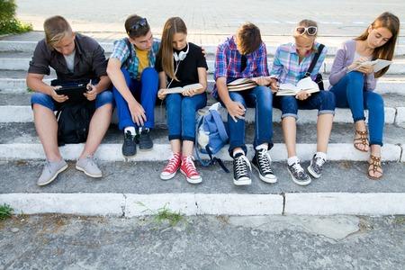 jovenes estudiantes: grupo de jóvenes estudiantes con libros y aparatos se sientan en los pasos en el parque