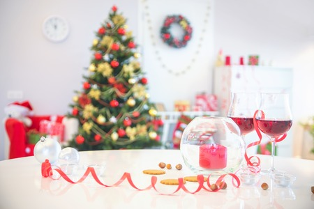 festively decorated table and the Christmas tree in the background Stock Photo
