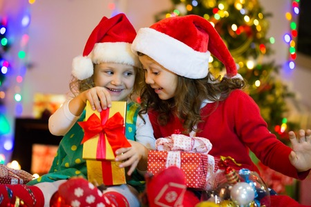 two little girls are opening presents around the Christmas tree