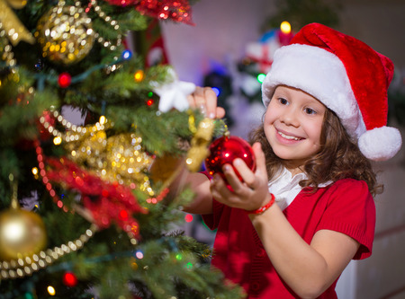 Little girl in Santa hat decorates a Christmas tree Stock Photo