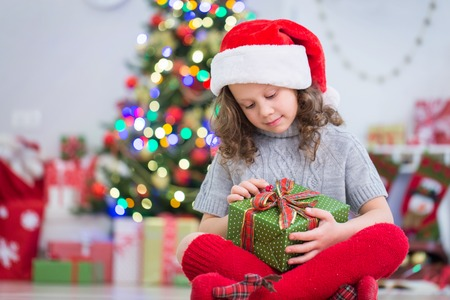 little girl in Santa hat packs presents under the Christmas tree